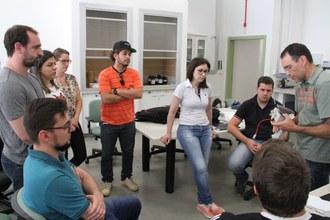 Na imagem nove pessoas observam o professor Luciano explicando funcionamento do Espectrômetro de Absorção Atômica.