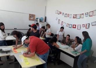 Na imagem três grupos de professores desenvolvem atividades utilizando cartolinas.