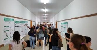 Na imagem um corredor onde vários trabalhos estão posicionados nas paredes e estudantes realizam apresentações de banners simultaneamente.