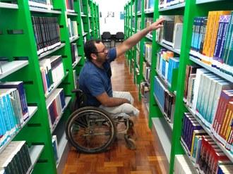 Na imagem um estudante cadeirante procura livros no acervo da biblioteca.