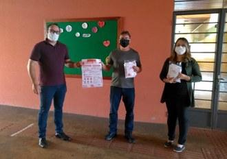 Na imagem três pessoas estão em pé, segurando nas mãos cartazes e pacotes contendo as cartilhas.