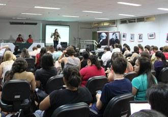 Na imagem pessoas sentadas em auditório acompanham apresentação de palestrante que está no palco.