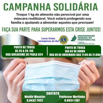 """Uma imagem de mãos segurando uma máscara, com os dizeres """"Campanha solidária - Troque 1 kg de alimento não perecível por uma máscara reutilizável. Você estará protegendo sua família e ajudando a alimentas aqueles que precisam!"""""""