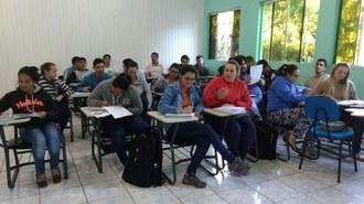 Pessoas sentadas em suas carteiras, em uma sala, durante aula.