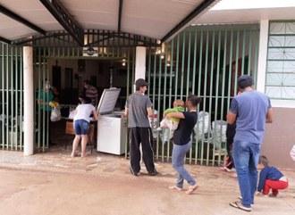 Na imagem algumas pessoas aguardam em fila para recebimento das cestas.