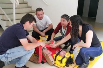 Na imagem uma pessoa deitada em maca sendo atendida por quatro pessoas, que simulam atendimento de primeiros socorros.