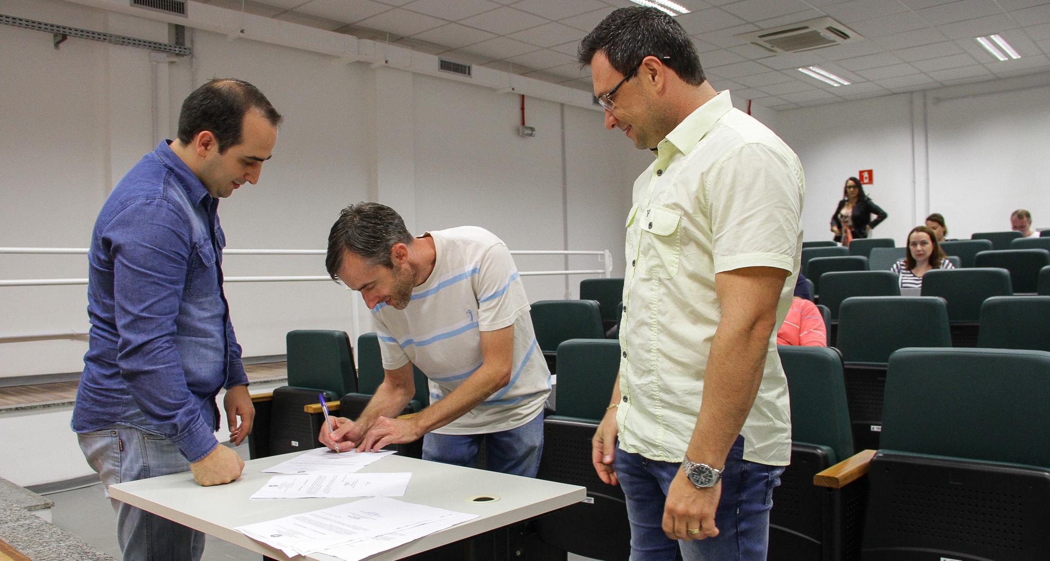 Três homens assinando documentos
