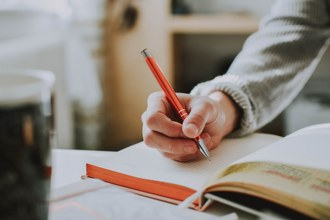 imagem de um caderno aberto encima de uma mesa e uma mão com uma lapiseira vermelha escrevendo nele
