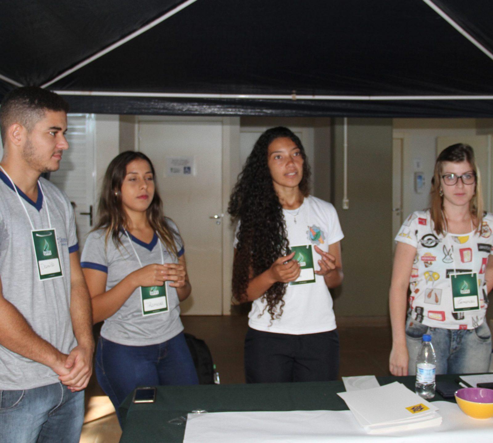 Aluna, ao lado de outros três alunos, realiza uma comunicação oral de trabalho científico