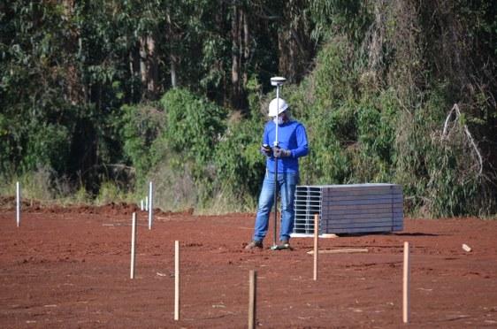 um homem de pé segura uma peça da usina fotovoltaica, atrás dele uma mata verde fechada.