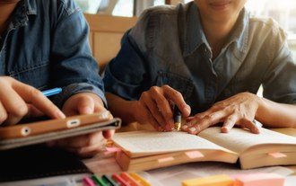 Fotografia de duas pessoas lado a lado. Na imagem só aparecem as mãos das pessoas que seguram livros e canetas