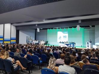 Na foto aparece várias pessoas sentadas de frente para o palco em que estão os formandos e a mesa de autoridades
